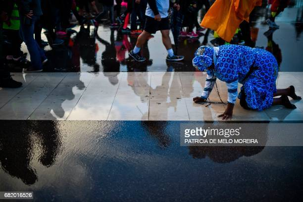 TOPSHOT An Angolan woman pays a promise walking on her knees at Fatima Sanctuary in Fatima central Portugal on May 11 2017 Two of the three child...