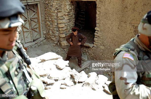 An angry and defiant Pashtun villager watches US Army troops search his village