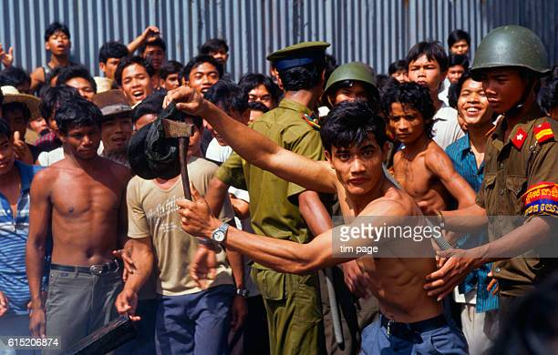 An angry crowd of cambodians demonstrating their hatred of Khieu Samphan the Khmer Rouge leader is restrained by Cambodian soldiers