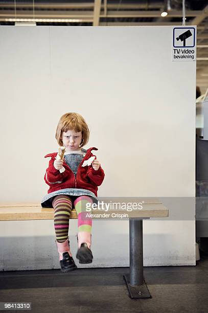 An angry little girl sitting on a bench Sweden.