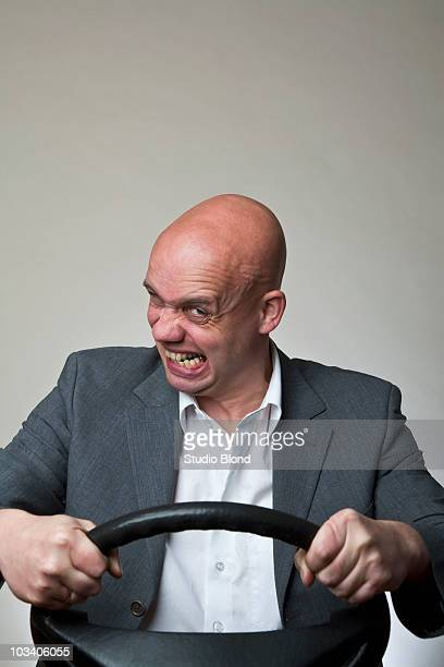 An angry man behind a car steering wheel
