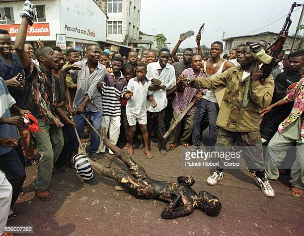 An angry mob drags the body of a burned Tutsi through the streets in front of soldiers
