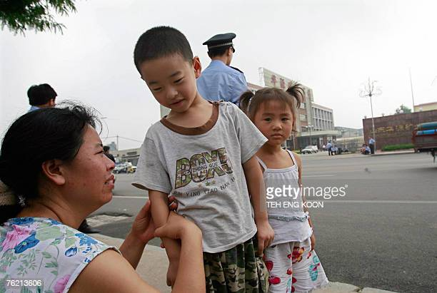 An angry relative weeps as she and her children wait outside the compound of Zhangzhuang mine in Xintai city eastern China's Shandong province 19...
