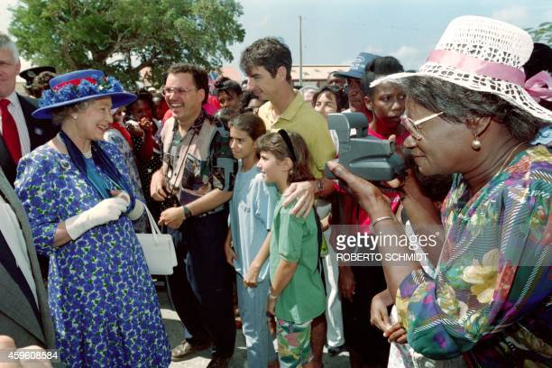 An Anguillan resident points her camera at Great Britain's Queen Elizabeth II as she greets residents and tourist lined up at a downtown street on...