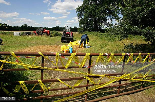 An animal health worker operates inside a secured farm area near Normandy in Surrey southeast England 08 August 2007 A probe into Britain's foot and...