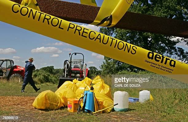 An animal health worker operates inside a secured farm area near Normandy in Surrey southeast England 08 August 2007 Investigators have found five...