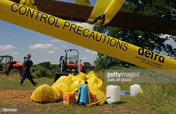 An animal health worker walks inside a secured farm area near Normandy in Surrey southeast England 08 August 2007 A probe into Britain's foot and...