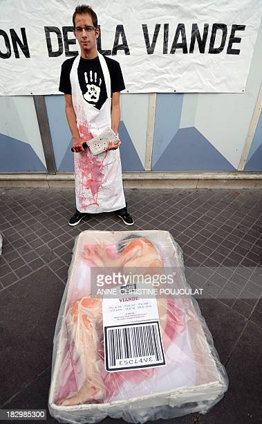 An animal rights activists from the association ALARM lays on punnet like a piece of meat as another one his dressed like a butcher to protest...