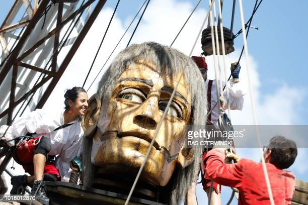 An animated marionette a socalled Giant of French street theatre company Royal de Luxe parades through the streets in the European Capital of Culture...