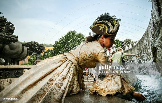 An animator cools off in a fountain during a hot summer day in downtown Moscow on June 25, 2021. - Moscow has been hit by a historic heat wave this...