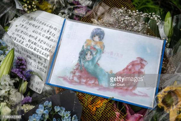 An anime cartoon drawing is laid amongst flowers and tributes near the Kyoto Animation Co studio building after an arson attack on July 19 2019 in...