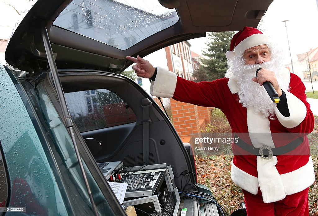 An announcer dressed as Santa Claus emcess from the back of a car during the 5th annual Michendorf Santa Run (Michendorfer Nikolauslauf) on December 8, 2013 in Michendorf, Germany. Over 900 people took part in this year's races, which included one for children and one for adults.