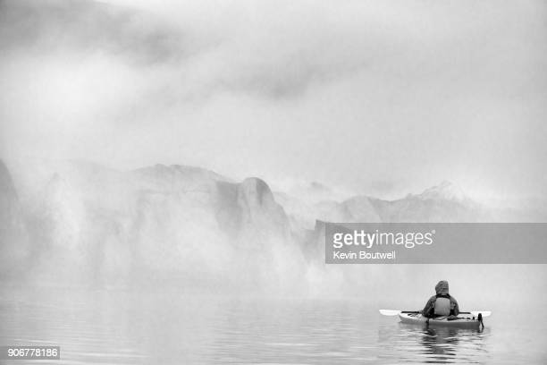 An anonymous kayaker admires the glacier face rising out of the mist