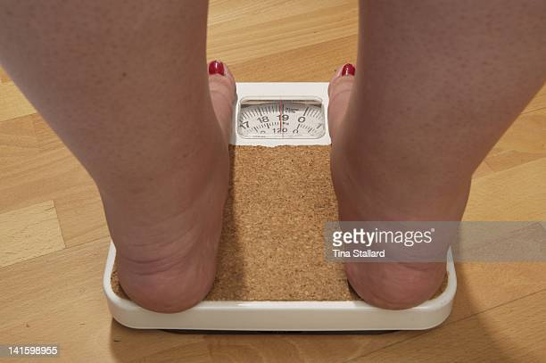 An anonymous woman on the scales before her weight loss surgery The scales stop at 19 stone but she weighs nearly 20 stone and is severely obese She...