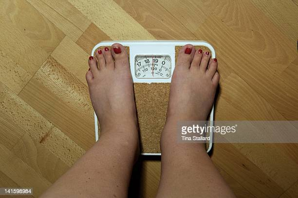 An anonymous woman on the scales before her weight loss surgery. The scales stop at 19 stone, but she weighs nearly 20 stone and is severely obese....