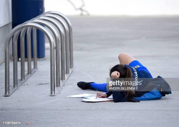 An Anorga KKE football school's player lies on the ground to do her homework following a training session in the Spanish Basque city of San Sebastian...
