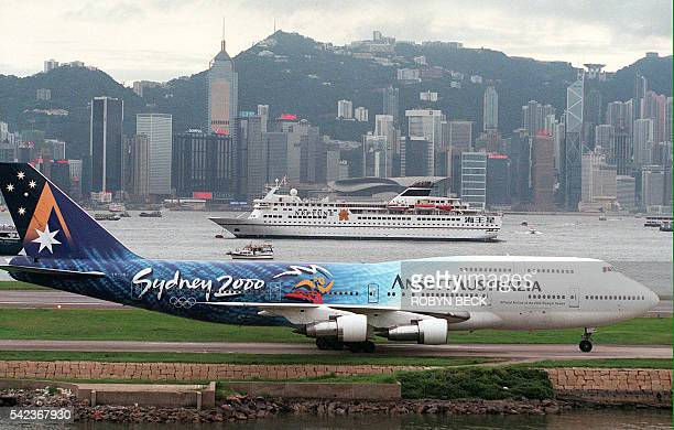 An Ansett Australia Boeing taxis on the runway against the skyline of Hong Kong Island late 05 July at Hong Kong's Kai Tak airport just hours before...