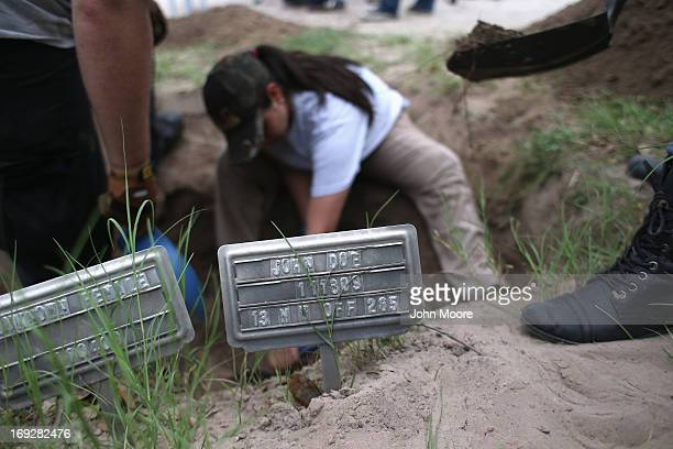 An anthropology student digs to reach the remains of suspected undocumented immigrants while exhuming bodies from a gravesite on May 22 2013 in...