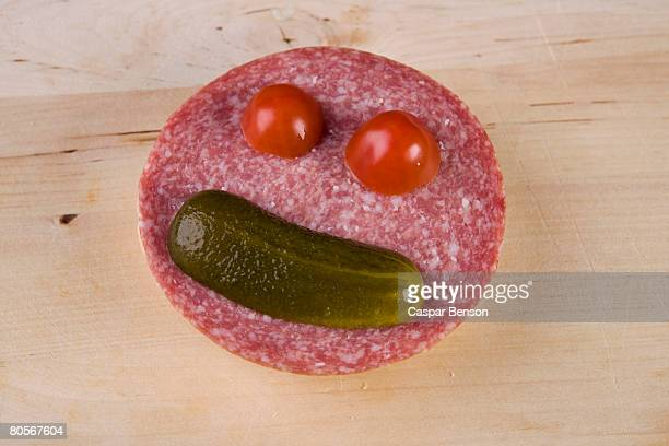 an anthropomorphic face on a slice of salami - sliced pickles stock photos and pictures