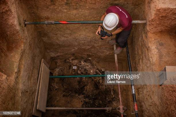 An anthtopologist volunteer photographs remains of the body number 66 found on the mass grave number 128 at the cementery of Paterna on August 29...