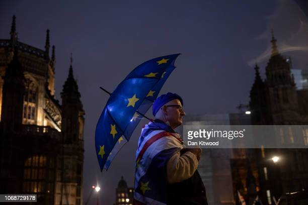 An anti Brexit campaigner holds an EU umbrella outside the Houses of Parliament on December 5 2018 in London England Cabinet met this morning after...