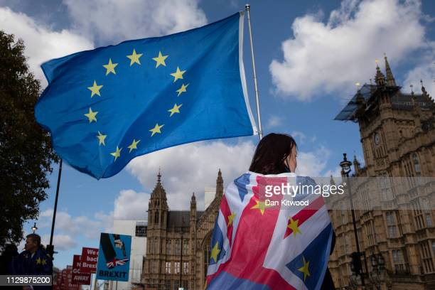 An anti Brexit protester stands with flags outside the Houses of Parliament in Westminster on March 11 2019 in London England MP's are due to get a...
