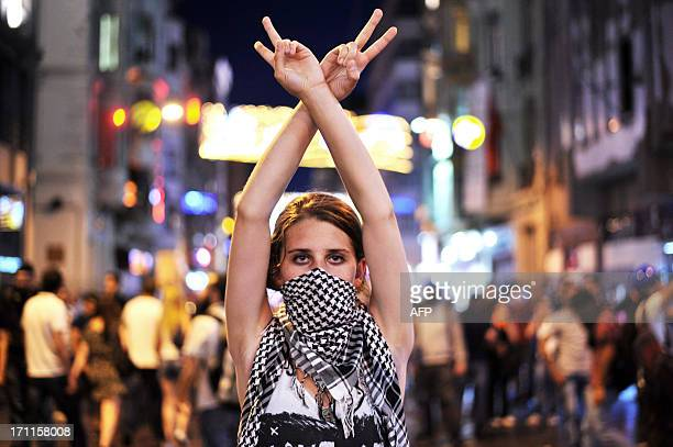 An anti goverment protester flashes a victory sign during the clashes between protestors and riot police on Taksim square in Istanbul on June 22 2013...