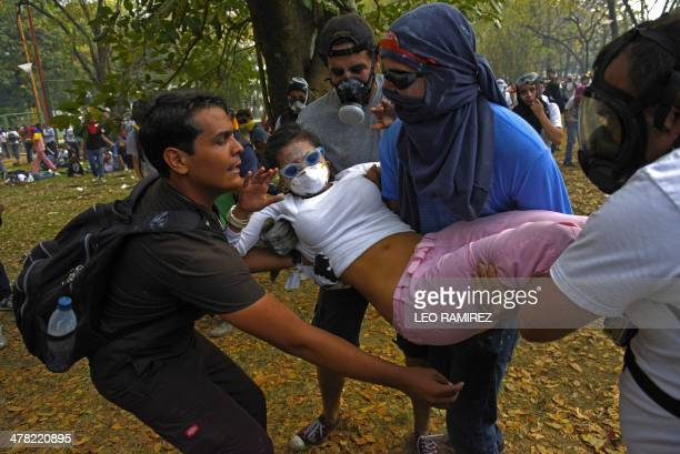 An anti government activist injured during clashes with the National Police is helped by mates in Caracas on March 12 2014 A young man was shot dead...
