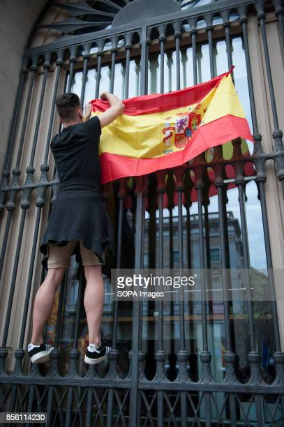 An anti Referendum putting a Spanish flag up in a Barcelona town hall window protester took to the streets of Barcelona to express their anger over...