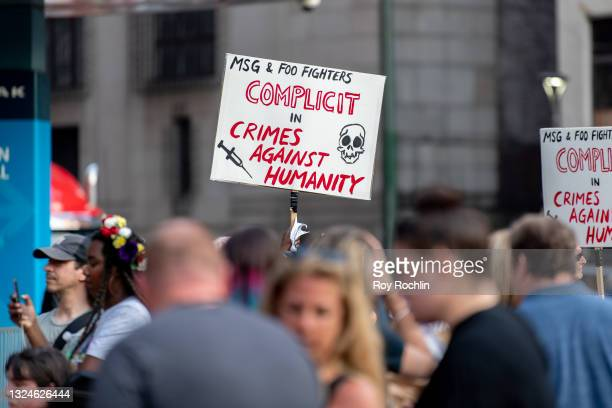 """An anti- vaccination activist holds a sign that reads """"MSG & FOO FIGHTERS COMPLICIT IN CRIMES AGAINST HUMANITY"""" as they protest the proof of..."""