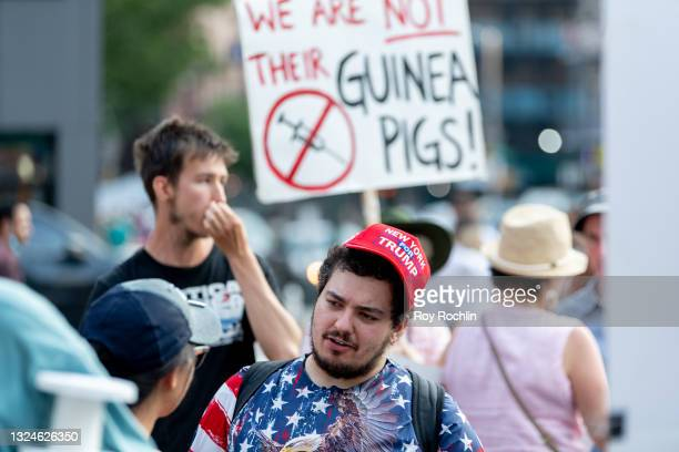 """An anti- vaccination activist wears a """"New York for Trump"""" hat as they protest the proof of vaccination requirement to get in to get into the Foo..."""