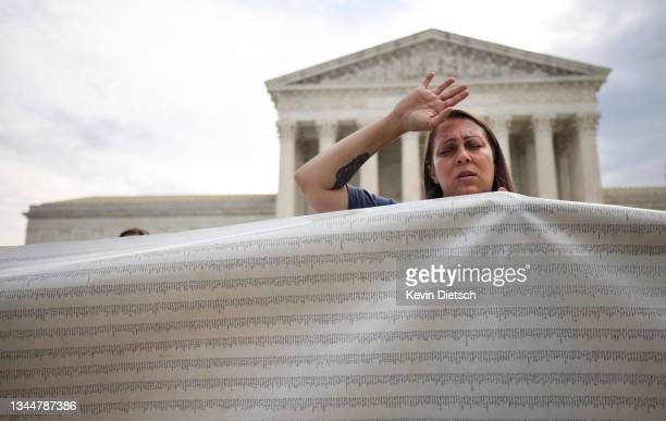 An anti-abortion activist holds a petition to end abortion during a demonstration outside of the Supreme Court on October 04, 2021 in Washington, DC....