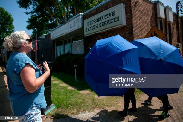 An antiabortion protester shouts her as a woman is escorted by Clinic Escorts into the Reproductive Health Services building in Montgomery Alabama on...