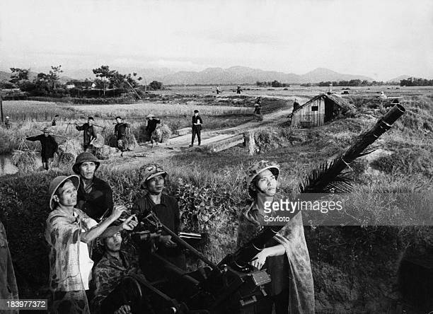 An antiaircraft People's militia unit of a North Vietnamese agricultural cooperative standing guard against an American air attack while farmers...