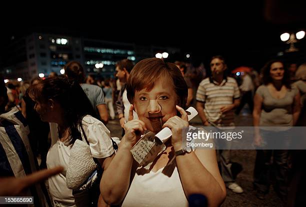 An antiausterity protestor wears a mask of Angela Merkel Germany's chancellor during a protest in Athens Greece on Monday Oct 8 2012 Greece's need...