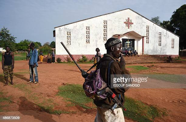 An AntiBalaka fighter smokes in front of a Catholic church where residents took refuge after an exSeleka rebels' incursion in Bouca on April 26 2014...