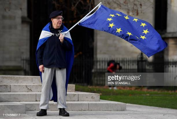 An anti-Brexit activist, draped in a Scottish Saltire flag, waves an EU flag as he demonstrates opposite the Houses of Parliament in London on...