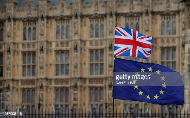 An anti-Brexit activist waves a Union and a European Union flag as they demonstrate outside the Houses of Parliament in central London on January 23,...