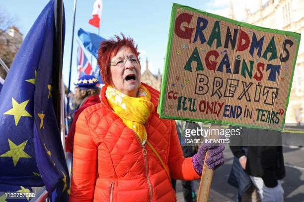 An antiBrexit campaigner holds up a 'Grandmas against Brexit' placard as she protests outside the Houses of Parliament in London on March 25 2019...