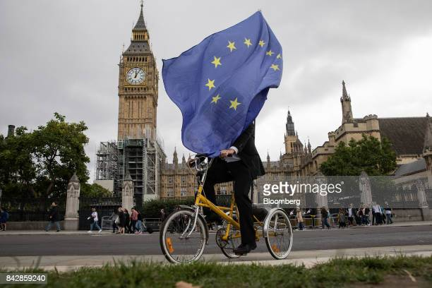 An antiBrexit demonstrator carries a European Union flag as he cycles outside the Houses of Parliament in London UK on Tuesday Sept 5 2017 UK Prime...