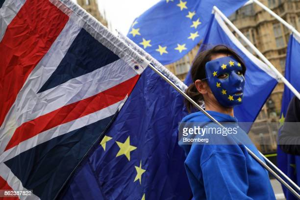 An antiBrexit demonstrator holds a Union flag also known as a Union Jack with a European Union flag outside the Houses of Parliament in London UK on...