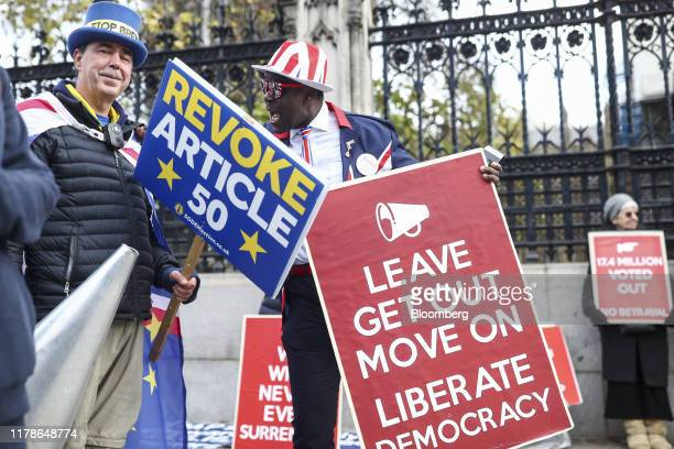An antiBrexit demonstrator left passes proBrexit demonstrators holding placards near the Houses of Parliament in London UK on Monday Oct 28 2019 The...