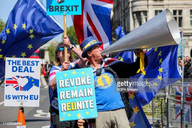 An AntiBrexit demonstrator seen with a huge vuvuzela European flags and placards protesting outside the Houses of Parliament against the UK leaving...
