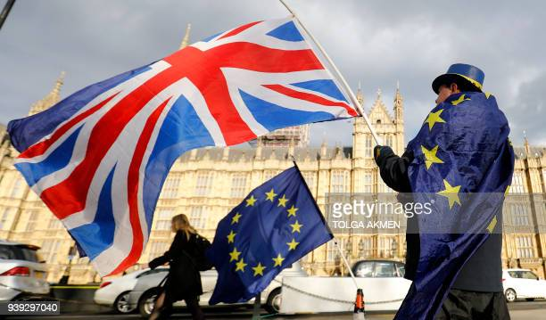 TOPSHOT An antiBrexit demonstrator waves a Union flag alongside a European Union flag outside the Houses of Parliament in London on March 28 2018...