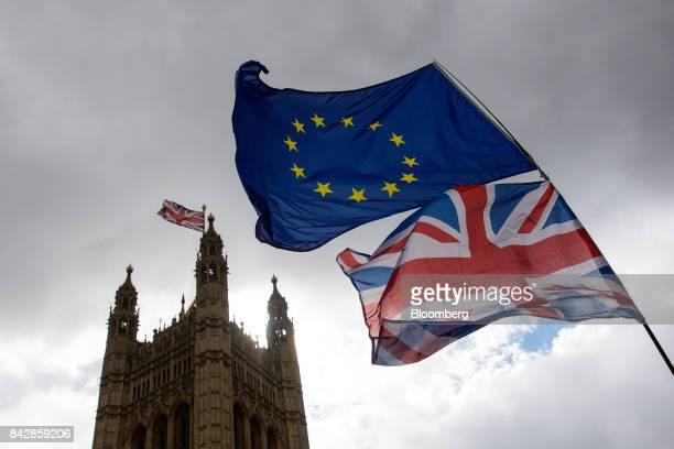 An antiBrexit demonstrator waves a Union flag also known as a Union Jack with a European Union flag outside the Houses of Parliament in London UK on...