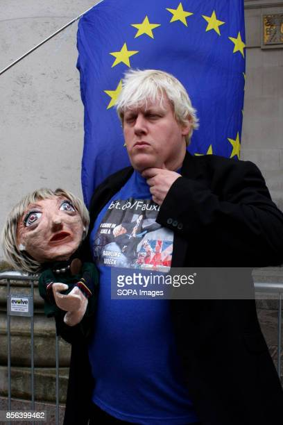 An AntiBrexit demonstrator who is a Boris Johnson Britains Foreign secretary lookalike postures with a Prime Minister Teresa May puppet during...