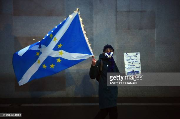 An anti-Brexit pro-Scottish independence activist holds a flag mixing the EU flag and the Scottish Saltire as she gathers for a small protest against...