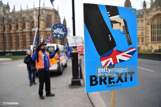 An antiBrexit protester holds a placard showing a graphic of a person shooting themself in the foot with the shoe on that foot decorated in the...