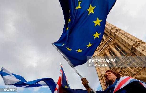 An antiBrexit protester holds an EU flag as they demonstrate outside the Houses of Parliament in London on March 14 2019 as MPs debate a motion on...