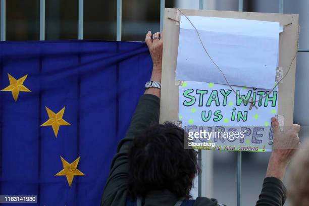 An antiBrexit protester holds up a placard as Boris Johnson UK prime minister meets Angela Merkel Germany's chancellor at the Chancellery in Berlin...